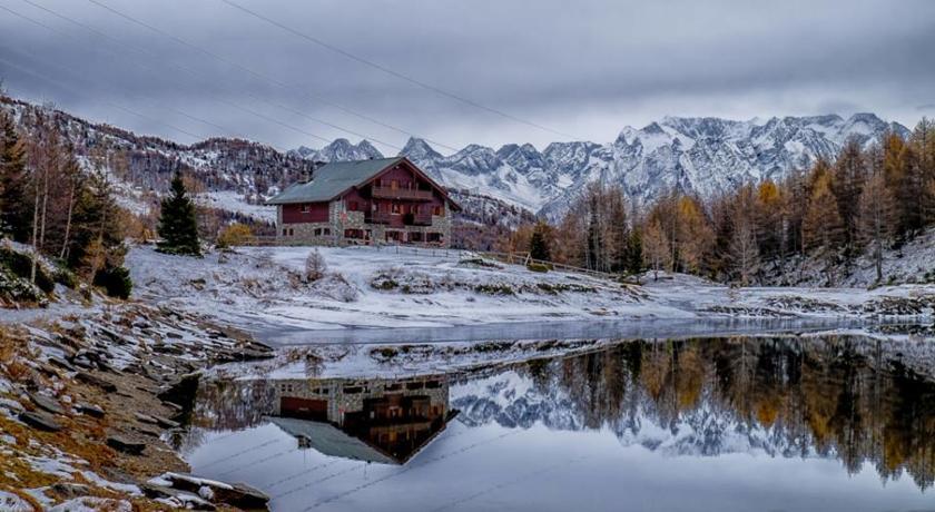 Italiaanse Alpen: afgelegen rifugio (berghut) aan een helder bergmeertje